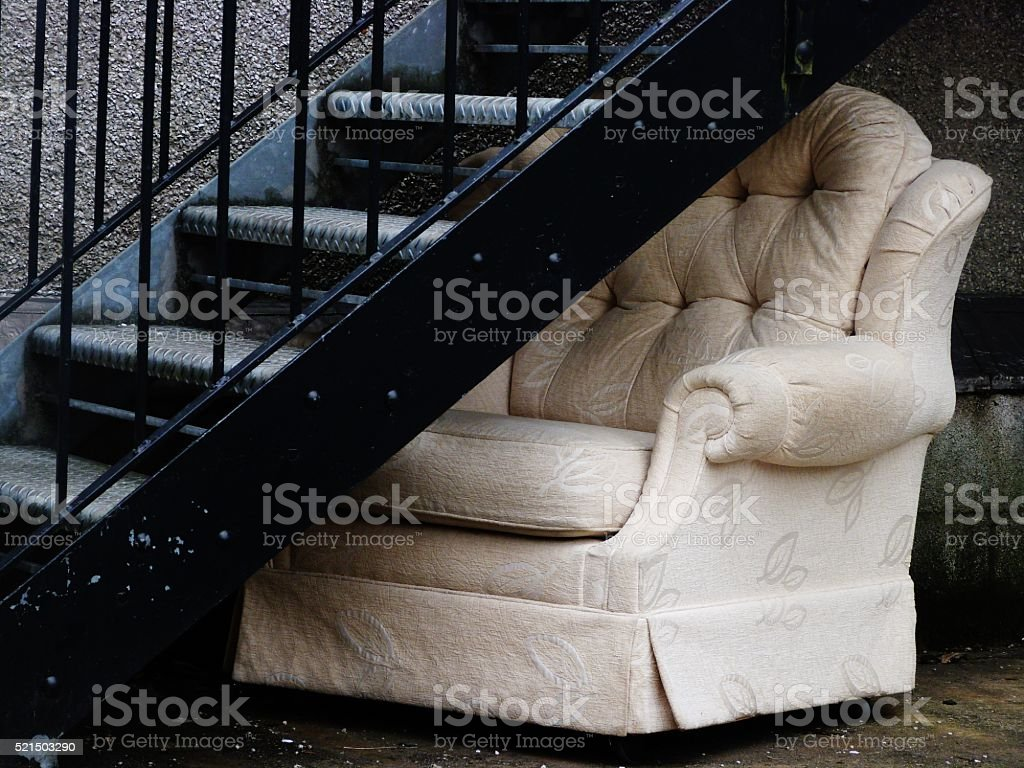 abandoned chair under staircase stock photo