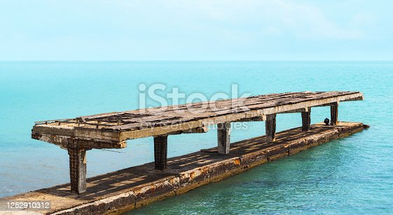Abandoned concrete covered pier. Old and broken pier into the sea