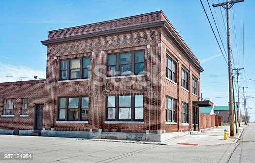 Abandoned, old, red brick, corner building that`s become part of urban decay or decline.
