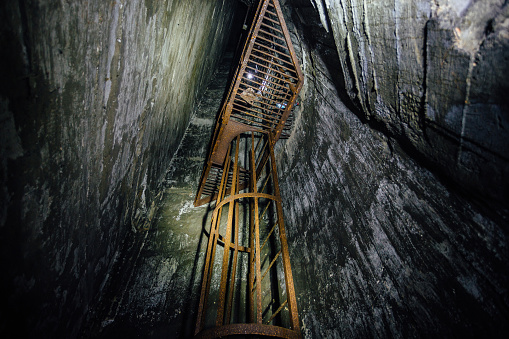 Abandoned deep vertical underground mine shaft. Old rusty iron ladder.
