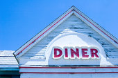 The roof and sign of an abandoned diner.  Rich blue hue from shooting with white balance set to tungsten.