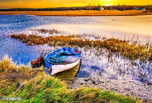 An old dory, half filled with water rests at the edge of a marsh during a rising tide on late November on Cape Cod.