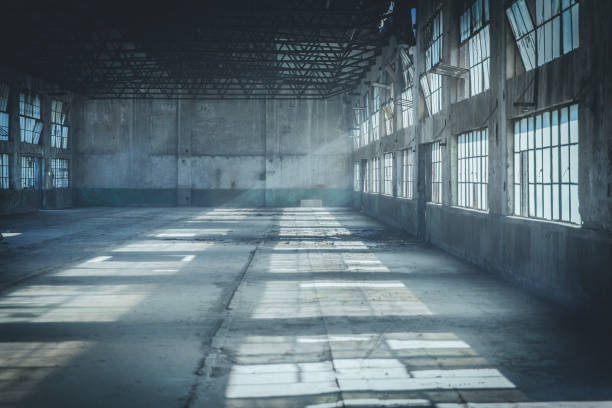 Abandoned Factory Building In Tyndall Effect Abandoned Factory Building In Tyndall Effect warehouse interior stock pictures, royalty-free photos & images