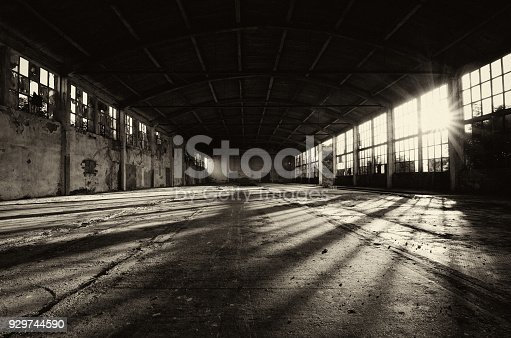 Long shadows in abandoned factory building on sunny summer day.