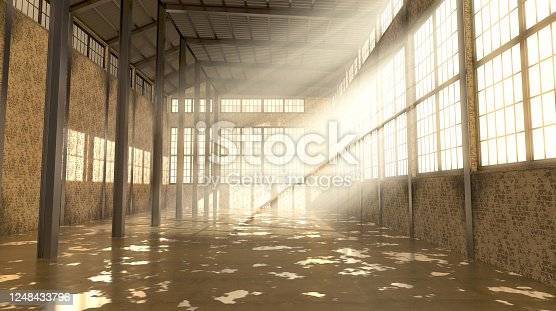 An empty and abandoned factory interior in the daytime with bright early morning light rays streaming in the windows - 3D render
