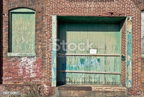 The boarded window and door at this abandoned factory indicate work has probably ceased here years ago. Variations in the brick indicate the building may have been altered in the course of its lifetime.