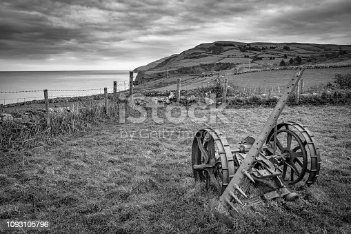A vintage piece of farm equipment rusting in a field in Ireland. This picture was taken along the Antrim Coast in Northern Ireland. it is in a place called Torr head