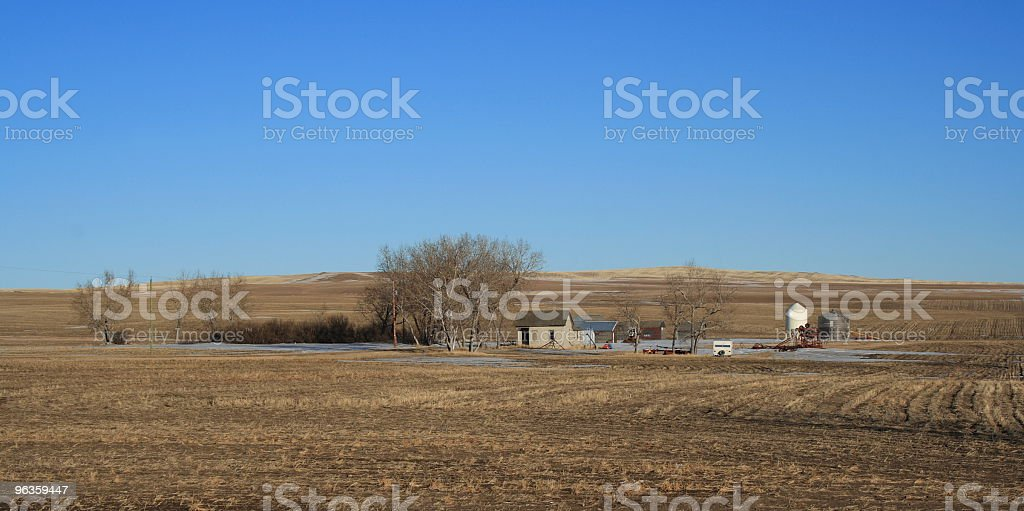 abandoned farm on prairie, clear blue sky above royalty-free stock photo