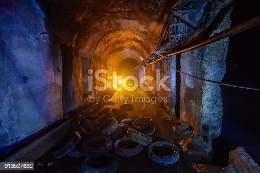 Abandoned flooded tunnel of cable collector, old rotten tires.