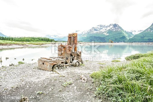 An antique forklift sits abandoned on the shores of Prince William Sound harbor.  The fork lift is a reminder of days gone by. Now it has become a part of the scenic beauty that can be found at the location of Valdez, before the Great Earthquake.