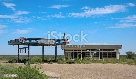 gas station from the 70's abandoned in the desert panhandle of Texas along Route 66, backed with a bright blue sky and emptiness