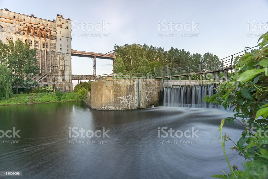 Abandoned Grain Silo with Waterfall and Whirlpool stock photo