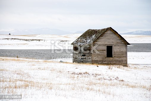 In abandoned, wooden homestead structure in a snow-covered field in front of a pond not yet frozen over