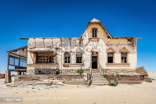 Abandoned House in Ghost Town Old Diamond Mine und deep blue desert sky. Desert sand entering the old abandoned and broken weathered house. Kolmanskop, Luderitz, Namibia, Africa.
