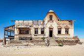 Abandoned House in Ghost Town Old Diamond Mine und deep blue desert sky. Desert sand entering the old abandoned and broken weathered house. Kolmanskop, Luderitz, Namibia, Africa.
