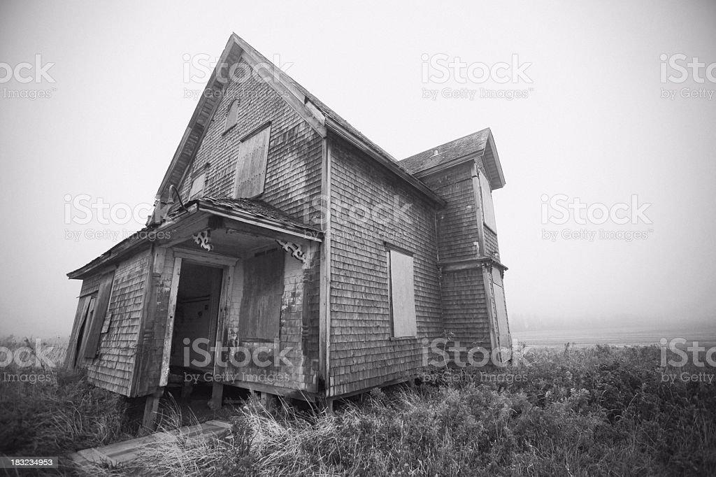 Casa abandonada em meio a um nevoeiro, um dia, monocromático. - foto de acervo