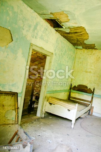 Room from abandoned house with broken down bed, roof that is falling in and peeling paint on the walls