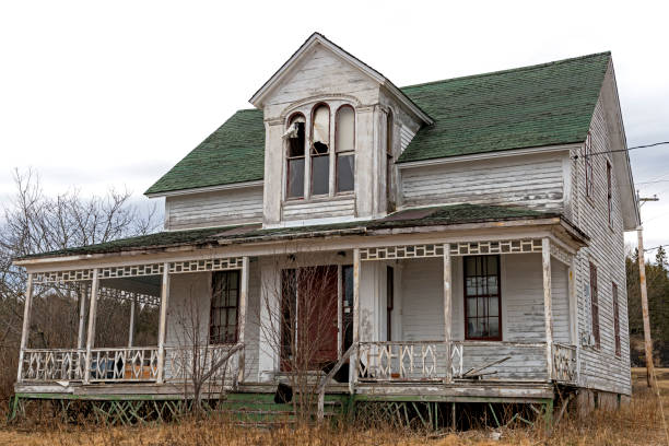 Abandoned House An old, abandoned house. Windows at the top are broken, the paint is peeling, and the front porch os falling down. Overcast sky. derelict stock pictures, royalty-free photos & images