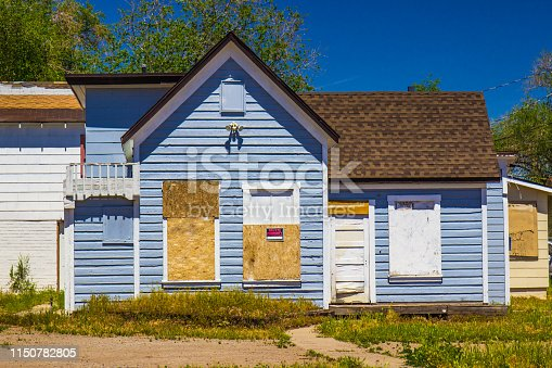 Abandoned House In Disrepair With Boarded Up Windows