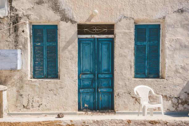 Verlassenes Haus mit weißer Wand und blauen Türen in Santorini, Griechenland – Foto