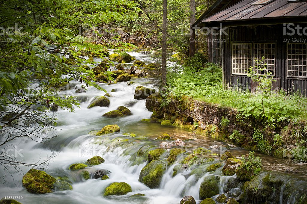 Abandoned hut next to aMountain stream in spring royalty-free stock photo
