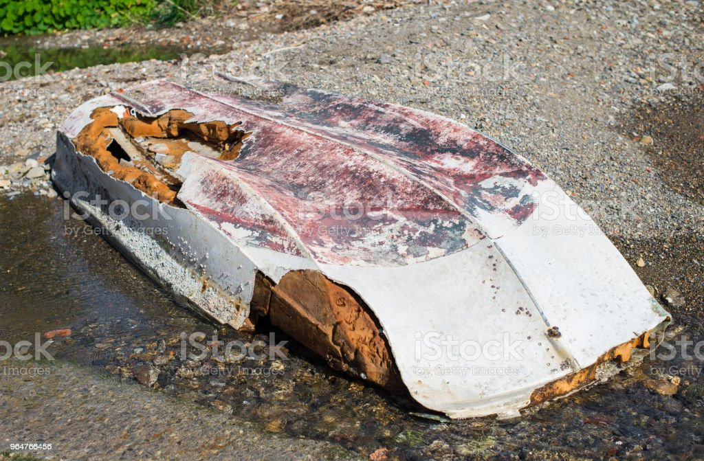 Abandoned inverted boat lying on the shore of the damaged hull royalty-free stock photo