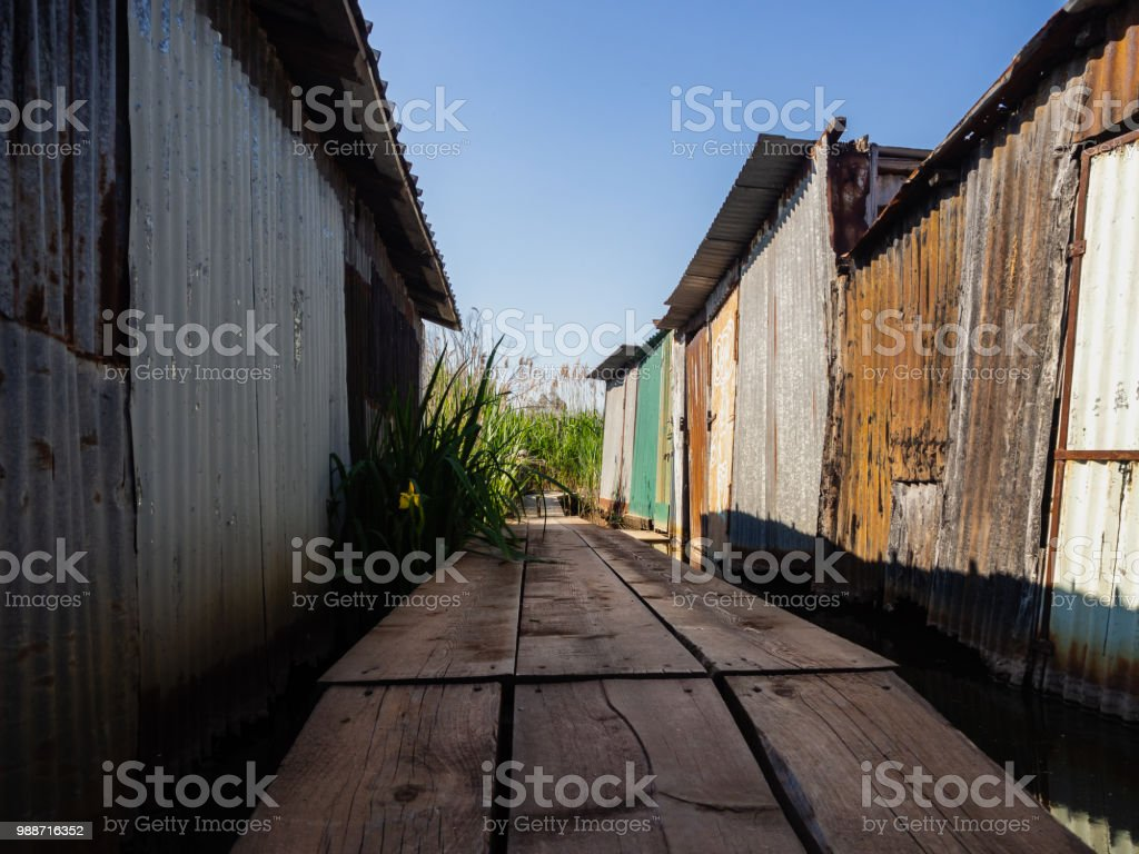 Abandoned iron shacks along the shore of the lake - foto stock