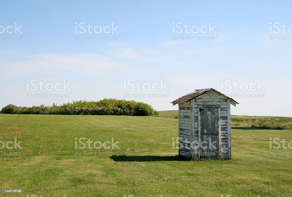 Abandoned Little Outhouse on the Prairie stock photo