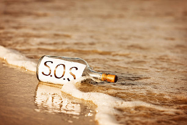 abandoned message in bottle on shore says sos - desert island stock photos and pictures