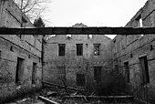 Old dirty ruined house, a grey old wall with broken windows