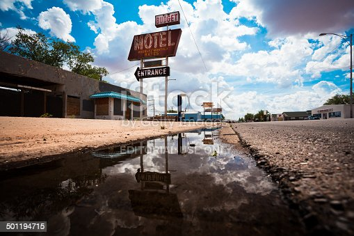 Holbrook, Arizona, United States - July 28, 2013: Sign of an abandoned motel reflecting on a puddle on the old route 66. The route 66 was one of the original highways within the U.S. Highway System. On June 27, 1985, it has been replaced in its entirety by the Interstate Highway System and many business had to close due to a decrease of customers.