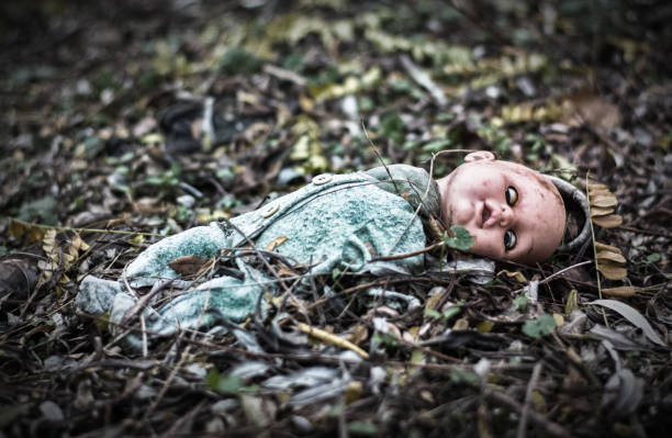abandoned old broken baby doll rots in scary forest stock photo