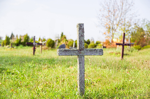Abandoned, old, wooden cross in the cemetery in sunny day.