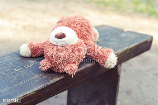 istock Abandoned on the wooden bench lonely teddy bear toy 515247341