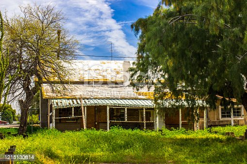 Abandoned One Level Home with Sagging Roof And Overgrown Front Yard