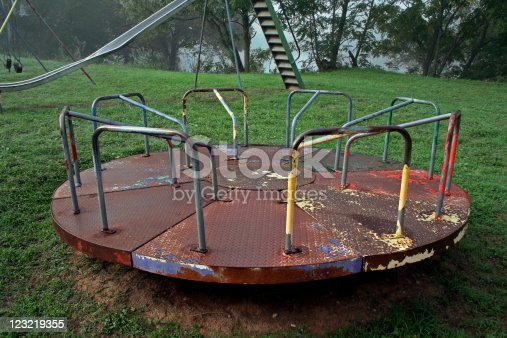 abandoned and rusted carousel playground equipment in a closed park