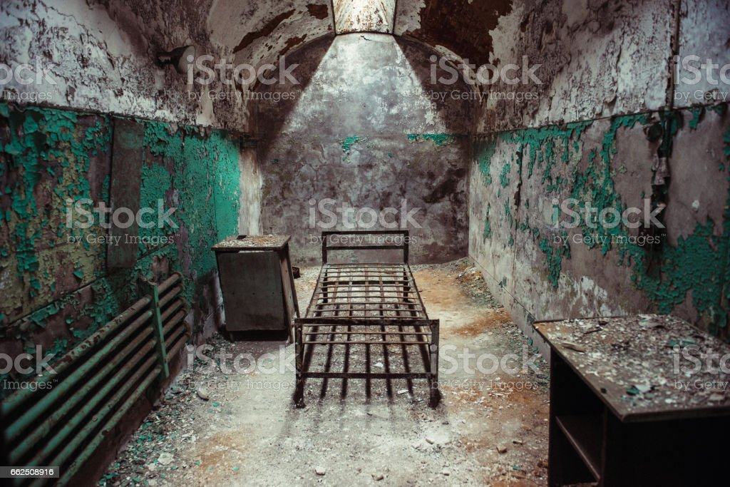 Abandoned prison cell room with old rusty bed frame stock photo