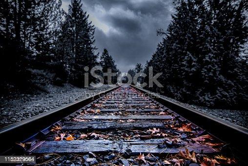 Dark abandoned railroad tracks with autumn leaves