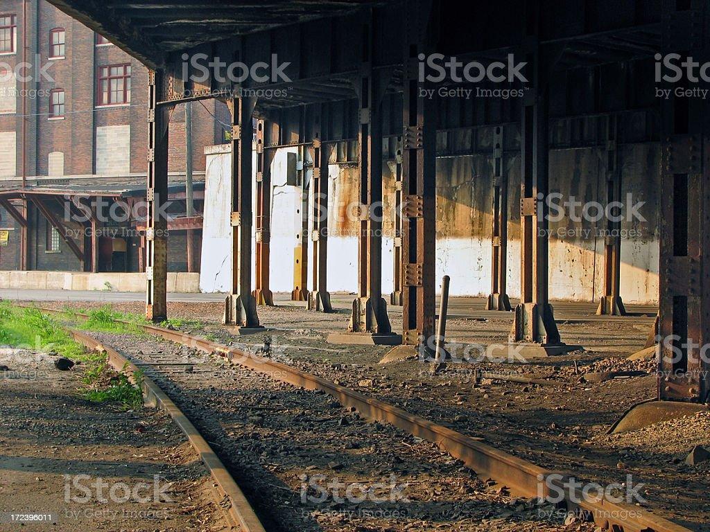 Abandoned Railroad Tracks Under Steel Bridge Near Warehouse royalty-free stock photo