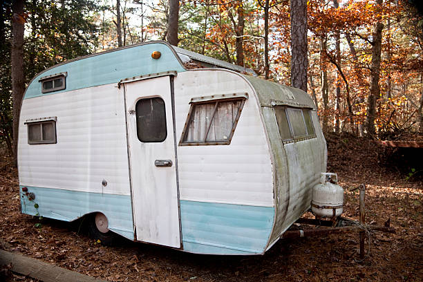 Abandoned Retro Travel Trailer, Mobile Home Old camper trailer rotting in the woods in a junkyard. Autumn color. terryfic3d stock pictures, royalty-free photos & images
