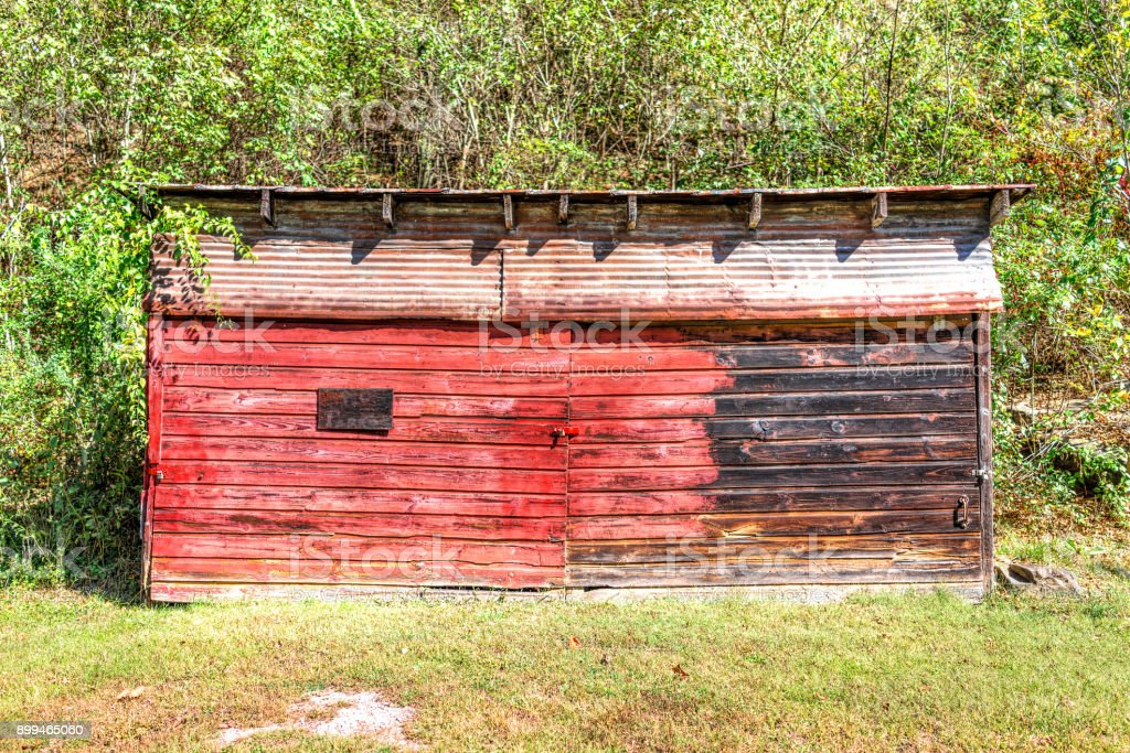 Abandoned retro vintage red barn shed exterior with locked doors and peeling paint stock photo