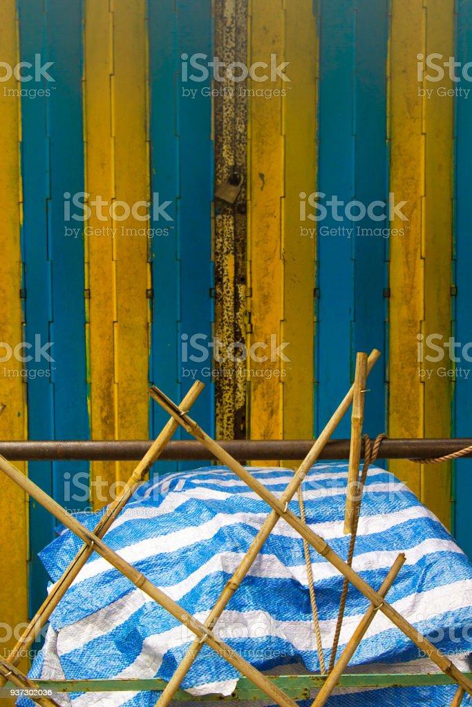 Abandoned rubbish beneath a striped tarpaulin, with bamboo screening. stock photo