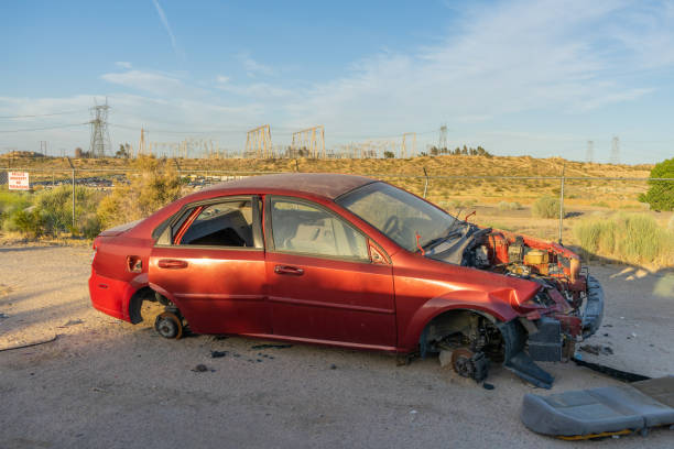 Abandoned sedan with missing engine and tires stock photo