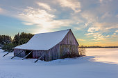 Weathered shed or barn in a snowy field in winter with the sun setting behind it.  Concepts could include nature, seasons, agriculture, others.