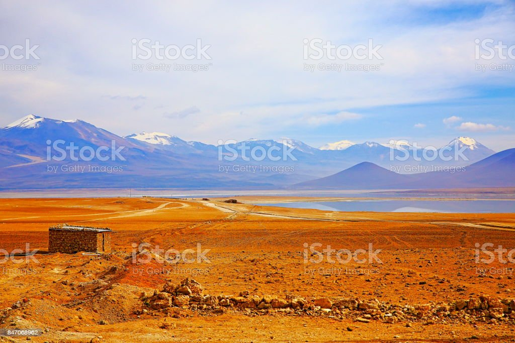 Abandoned shelter in Bolivian Andes altiplano at sunrise and volcanoes  near laguna verde, Idyllic Atacama Desert, snowcapped Volcanic steppe puna landscape panorama – Potosi region, Bolivian Andes, Chile, Bolívia and Argentina border stock photo