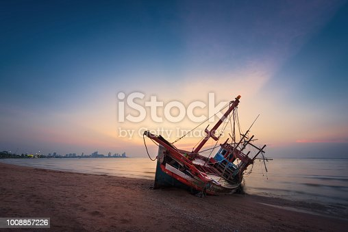 Abandoned shipwreck of wood fishing boat on beach at twilight time