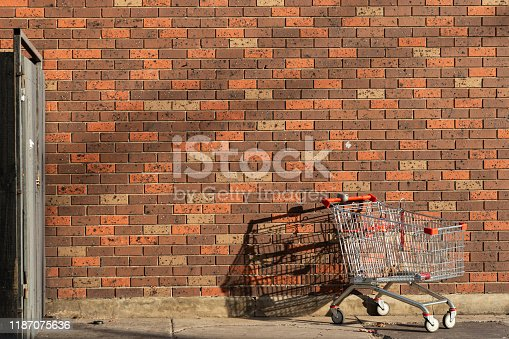 istock Abandoned Shopping Cart Left Behind Against Red Brick Wall 1187075636