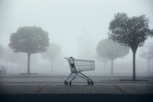 Abandoned shopping cart on parking lot in thick fog. Themes shopping, financial crisis and gloomy weather.