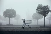 istock Abandoned shopping cart on parking lot in thick fog 1287629056