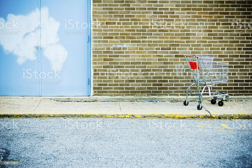 Abandoned Shopping Cart  on Sidewalk Outside Store stock photo